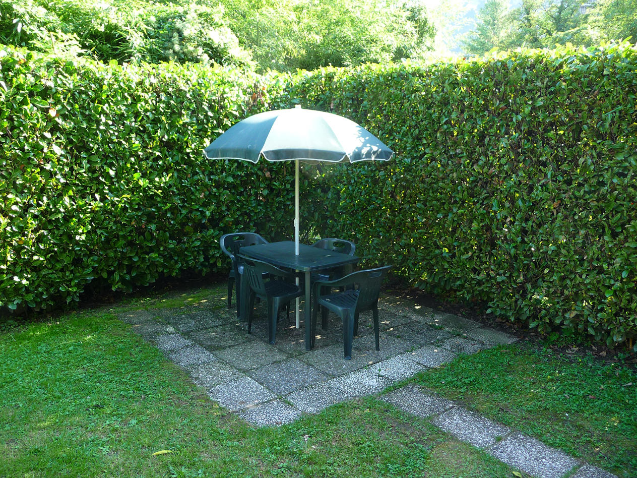 private garden with table , chairs and big umbrella